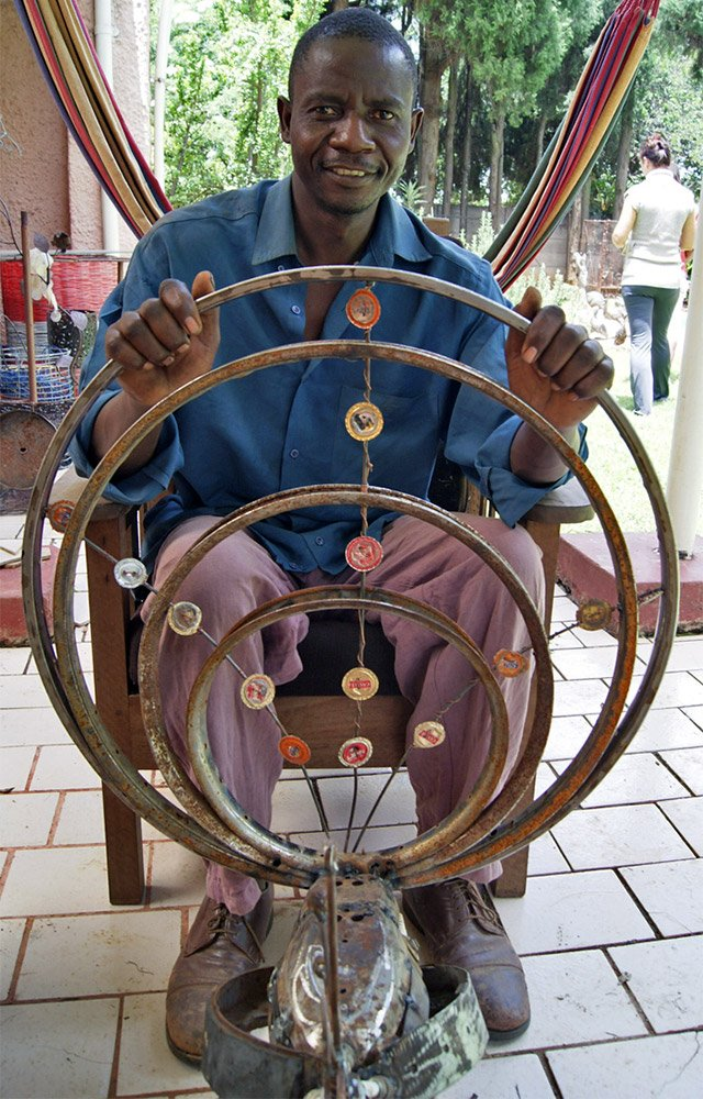 Joram sitting facing camera with his peacock sculture